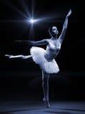 Balletttänzer im weißen Ballettröckchen, das auf einem Bein aufwirft lizenzfreie stockbilder