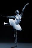 Balletttänzer im weißen Ballettröckchen, das auf einem Bein aufwirft lizenzfreie stockfotos