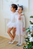 Balletttänzerumarmung mit zwei Jungen nahe Weihnachtsbaum Stockfotos