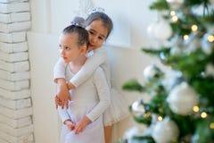 Balletttänzerumarmung mit zwei Jungen nahe Weihnachtsbaum Lizenzfreie Stockbilder