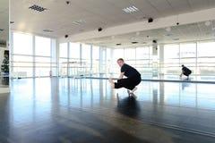 Balli l'istruttore che si siede sulla cordicella con le inclinazioni in avanti Immagini Stock