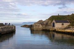 Ballintoy的小港口北爱尔兰北部安特里姆海岸的有它的石被修造的船库的在一天在春天 免版税库存照片