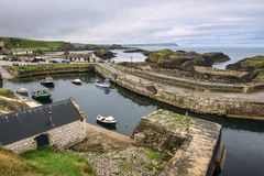 Ballintoy harbor in Northern Ireland. Ballintoy harbor with boats and ocean in the background located at the Northern coast of County Antrim, which was used as a stock photo