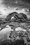 Ballintoy Sea Arch in Black and White. This is the sea arch at Ballintoy on the north coast of Ireland. This was taken at low tide leaving tidel pools reflecting royalty free stock photos