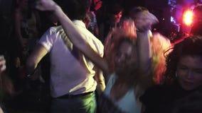 Ballo attraente delle ragazze sul partito in night-club Saltando, mani di aumento intrattenimento riflettori stock footage
