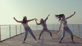 Ballo del bottino dall'adolescente delle ragazze su un ancoraggio di legno al mare video d archivio