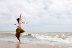 Ballo felice della donna sulla spiaggia Fotografia Stock