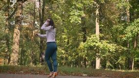 Ballo felice di bella ragazza castana caucasica che artisticamente sta muovendosi indietro in Sunny Park sul fondo degli alberi archivi video