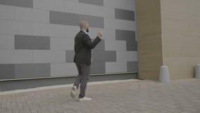 Ballo sicuro del freestye di dancing dell'uomo d'affari sul suo modo lavorare alla via - stock footage