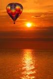 Ballon à air chaud au-dessus d'un coucher du soleil d'or de lac Photos libres de droits
