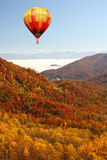 Ballon à air chaud au-dessus des montagnes dans des couleurs d'automne Photos stock