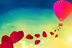 Ballon à air chaud avec les coeurs rouges volant de Photo stock
