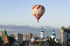 Ballon à air chaud blanc rouge dans le plan rapproché sans nuages de ciel bleu bas au-dessus de la ville Photographie stock libre de droits