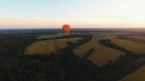 Ballon à air chaud dans le ciel au-dessus d'un champ Photo libre de droits