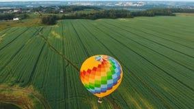 Ballon à air chaud dans le ciel au-dessus d'un champ Photographie stock