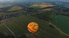 Ballon à air chaud dans le ciel au-dessus d'un champ Photos stock
