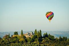 Ballon à air chaud de flottement au-dessus d'une villa toscane photos libres de droits