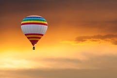 Ballon à air chaud en vol sur le fond de ciel de coucher du soleil Image libre de droits