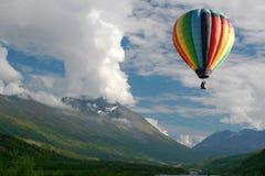 Ballon à air chaud flottant près des montagnes Photographie stock