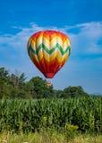 Ballon à air chaud formé par larme colorée au-dessus de champ de maïs sur Sunny Day avec les arbres et le ciel bleu nuageux Photographie stock