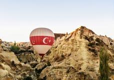 Ballon à air chaud volant au-dessus de la vallée pendant le matin Cappadocia La Turquie Photos stock
