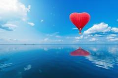 Ballon à air d'un rouge ardent sous forme de coeur Photos stock