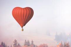 Ballon à air de D sous forme de vol de coeur dans la forêt brumeuse Photographie stock libre de droits