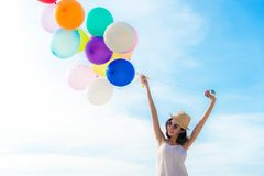 Ballon asiatique de sourire de participation de main de froid de femme de mode de vie sur la plage Détendez et appréciez dans des photos libres de droits