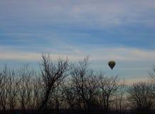 Ballon coloré avec le vol de panier au-dessus des silhouettes d'arbres contre le ciel de matin en tant que fond d'amusement d'hiv Photos stock