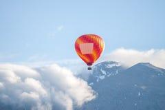 Ballon coloré d'air au-dessus des nuages et des montagnes Photographie stock libre de droits