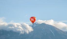 Ballon coloré d'air au-dessus des nuages et des montagnes Images libres de droits