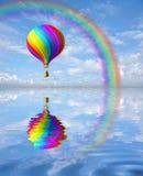 Ballon coloré d'air chaud dans le ciel bleu avec l'arc-en-ciel Photos stock