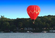 Ballon d'air chaud au-dessus de lac photo stock