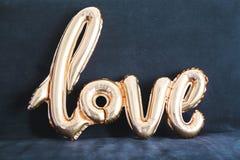 Ballon d'or formé de l'amour de mot sur le fond foncé Images stock