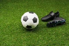 Ballon de football avec des paires de bottes noires sur l'herbe Image libre de droits