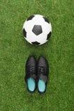 Ballon de football avec des paires de bottes noires sur l'herbe Photo libre de droits