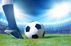 Ballon de football avec le joueur de pieds sur le terrain de football images libres de droits