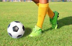 Ballon de football avec le pied de coups de pied de joueur Images libres de droits