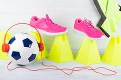 Ballon de football avec les écouteurs rouges, parmi une rangée des cônes jaunes et des espadrilles roses, sur un fond gris Photo stock