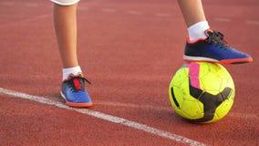 Ballon de football avec leur garçon de pieds sur le terrain de football banque de vidéos