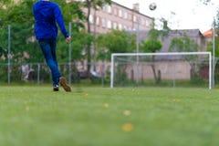 Ballon de football avec ses pieds sur le terrain de football photographie stock