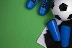Ballon de football, bottes bleues, crampons, T-shirt blanc et shorts noirs sur le fond vert Configuration plate, vue supérieure photos stock