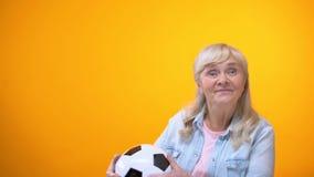 Ballon de football de capture de femme agée positive, énergie de la vie et fond de vivacité banque de vidéos