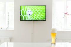 Ballon de football dans le but à la télévision et à un verre de bière de blé sur une table Photos libres de droits