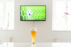 Ballon de football dans le but à la télévision et à un verre de bière de blé sur une table Images stock