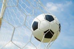 Ballon de football dans le but après shooted Photographie stock libre de droits