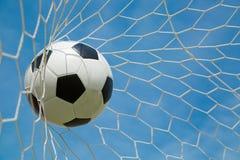 Ballon de football dans le but après shooted Photo stock