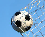Ballon de football dans le filet de but au-dessus du ciel bleu. Le football. Photographie stock libre de droits