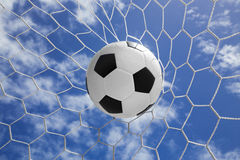 Ballon de football dans le filet de but avec le ciel bleu Photographie stock libre de droits
