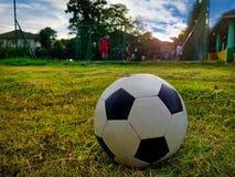 Ballon de football en gros plan sur le champ avec des personnes jouant le football dans éloigné Photos stock